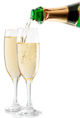 Champagne being poured into glass or flute, isolated on a white background. Stock Photo
