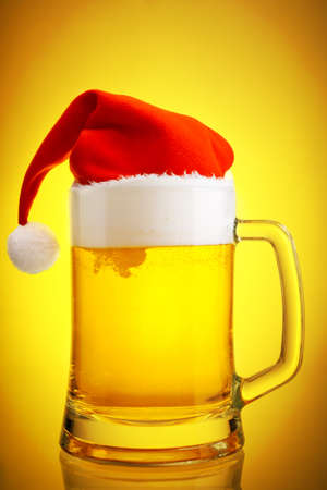moistness: Beer and hat of Santa Claus on a yellow background