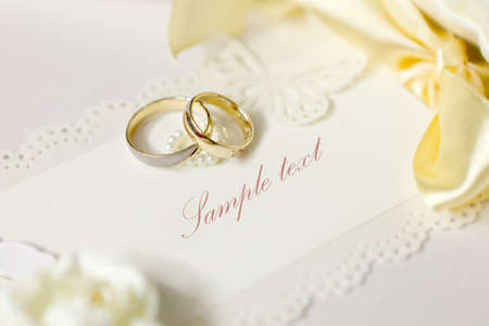 wedding accessories: Wedding rings and wedding invitation with bow Stock Photo