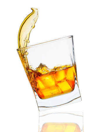 glass of whiskey with ice cubes splashing out over white Stock Photo