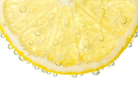 Bubbles on a lemon segment in soda water