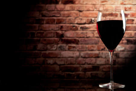 glass brick: glass of wine on the background of a brick wall Stock Photo