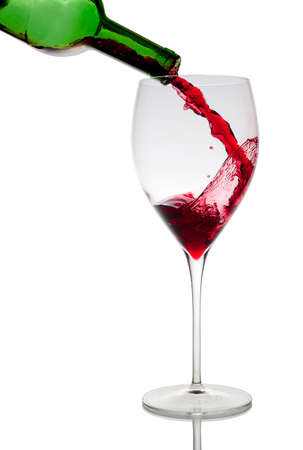 Pouring red wine in glass goblet isolated on white Stock Photo