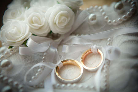 Two wedding rings with white flower in the background. Standard-Bild