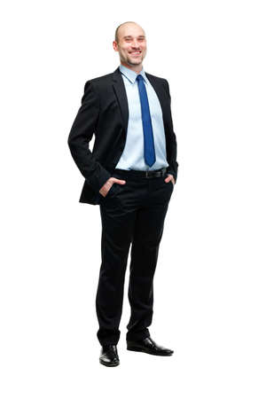 Full length portrait of a young businessman standing with his hands in the pockets. Stock Photo