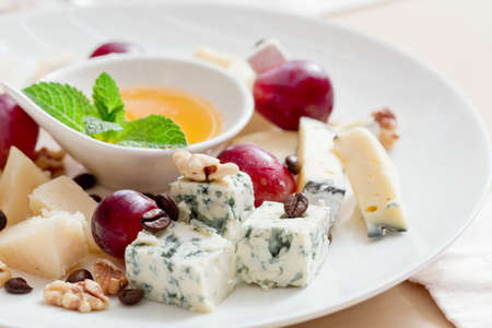 Still-life cheese platter with nuts and grapes Stock Photo - 20243052