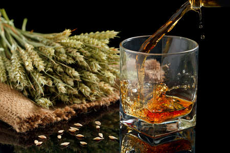 Pouring whiskey into glass, on black background Stock Photo