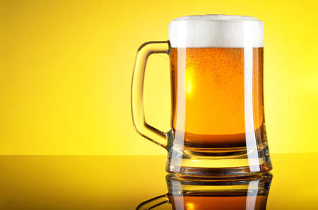 Glass of beer close-up with froth over yellow background Stock Photo - 20871696