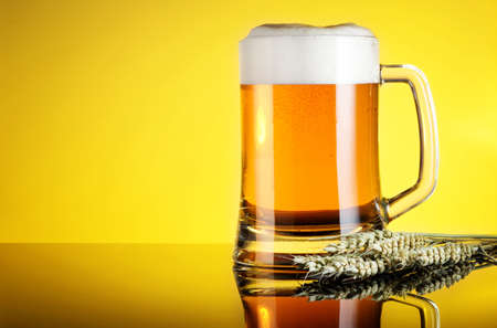 Glass of beer close-up with froth over yellow background Stock Photo - 20871698