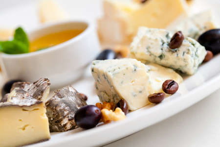Still-life cheese platter with nuts and grapes Standard-Bild