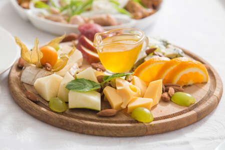 Still-life cheese platter with nuts and grapes Stock Photo