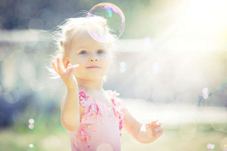 A little girl catches soap bubbles in the summer park Stock Photo