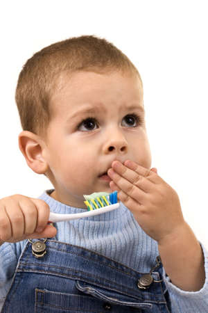 Young boy brushing his teeth with toothbrush, isolated in white Imagens
