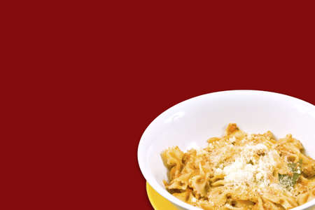 Farfalle with chesse in red background photo