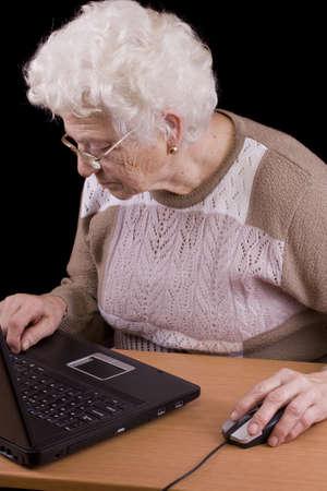 Senior woman reading on laptop computer  photo