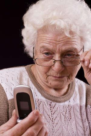 vejez: Anciana y el tel�fono m�vil aislado en fondo negro