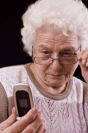 very: Old woman and the mobile phone isolated in black background