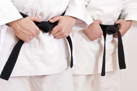 defensa personal: Atleta de dos artes marciales atar el nudo a su cintur�n negro.  Foto de archivo