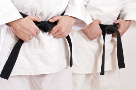 self defense: Two martial arts athlete tying the knot to his black belt