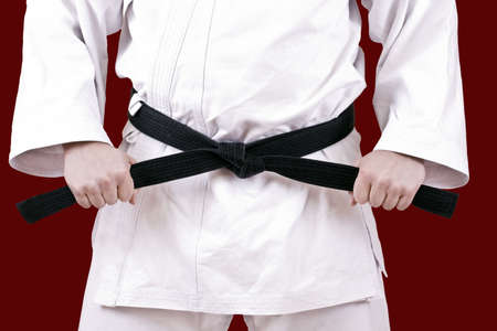 Martial arts athlete tying the knot to his black belt