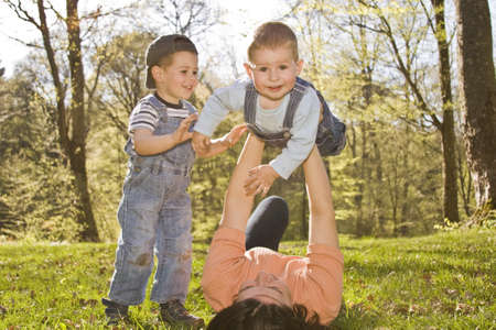 single mother: family lifestyle portrait of a mom with their two kids having fun outdoors  Stock Photo