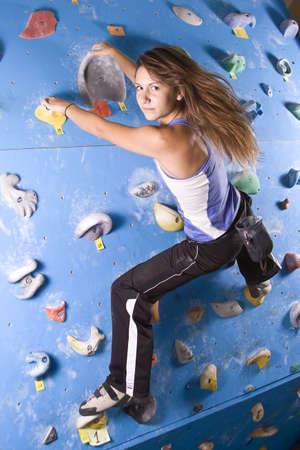 bouldering: Ragazza bella, giovane, atletica, arrampicata su una parete di arrampicata indoor