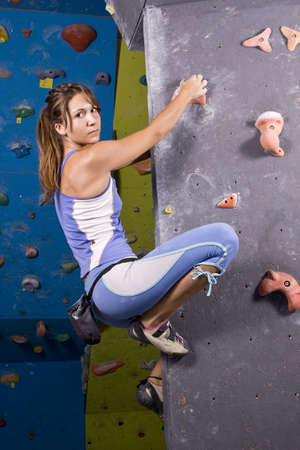 carabineer: Pretty, young, athletic girl climbing on an indoor rock-climbing wall