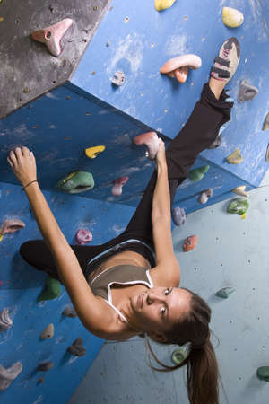 climbing wall: Pretty, young, athletic girl climbing on an indoor rock-climbing wall