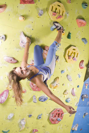 Pretty, young, athletic girl climbing on an indoor rock-climbing wall Stock Photo - 7697963