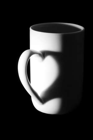 tea break: Coffee cup  over black background, heart form in shadow