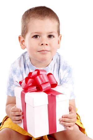 Little boy holding gift box isolated on white  photo