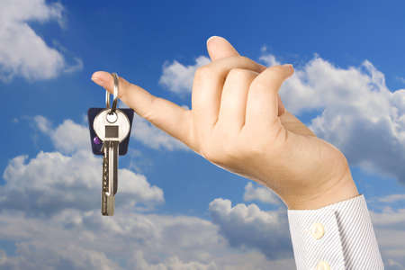 Woman holding a key for a house on a keychain, sky in background Stock Photo - 7997526