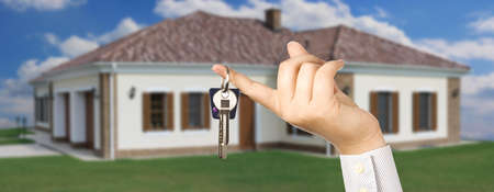 Woman holding a key for a house on a keychain, house in background Stock Photo - 7999936