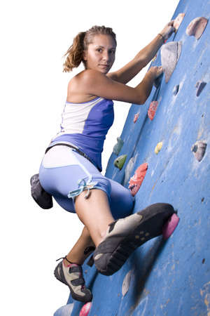 Pretty, young, athletic girl climbing on an indoor rock-climbing wall  photo