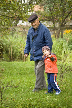 Portrait of small boy helping a old man on walking - Outdoor photo