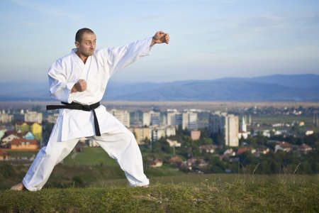 Young adult men practicing Karate outdoor, city in background photo