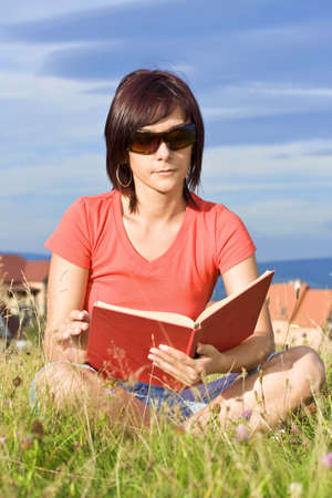 Young woman lying on the grass and reading book outdoor  photo