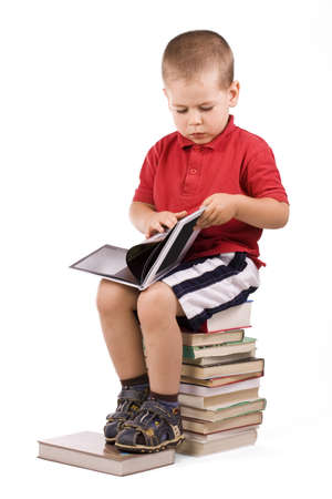 three year old boy sitting on pile of books, reading Stock fotó