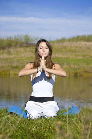 Slender young woman doing yoga exercise outdoors.  Stock Photo - 8125607