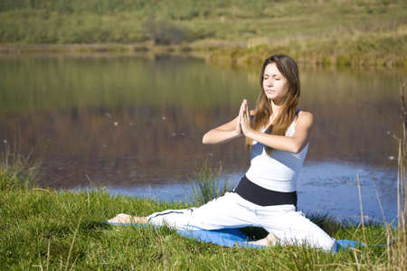 young woman doing yoga exercise outdoors.  photo