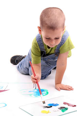 young boy painting over white photo