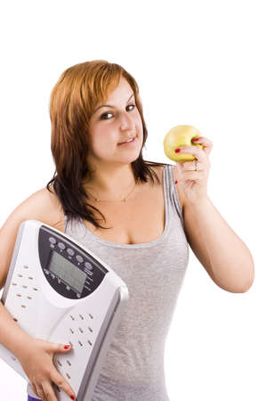 Young woman eating apple and carrying a weight scale over white background Stock Photo - 8306567