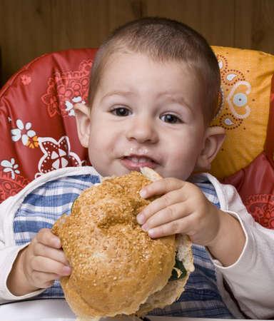 The little happy boy eating a tasty hamburger Stock Photo - 8306621