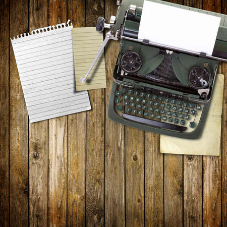 Old vintage typewriter with a blank sheet of paper inserted in wood background Stock Photo - 8592453