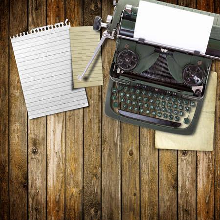 typewriter: Vieja m�quina de escribir vintage con una hoja en blanco de papel insertada en madera de fondo