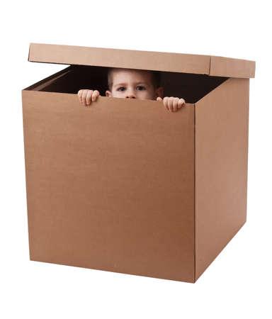 cajas de carton: Ni�o peeping sobre una caja de cart�n marr�n