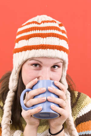 Young woman in winter hat with cup of hot drink photo
