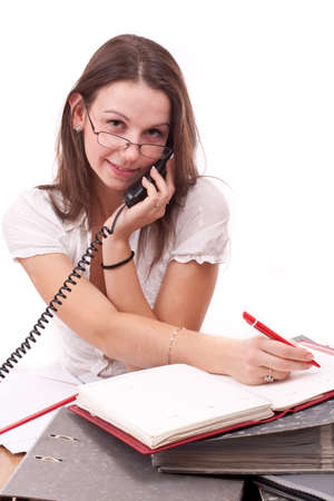 trait: trait of a smiling business woman sitting in office and calling by telephone  Stock Photo
