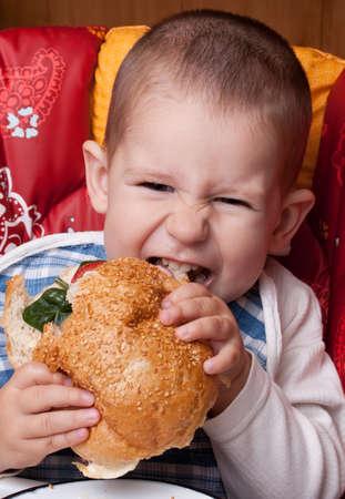 Little happy boy eating a tasty hamburger Stock Photo - 8690143