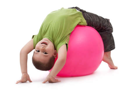 Little boy doing gymnastic exercises with a large rubber ball  Stock Photo